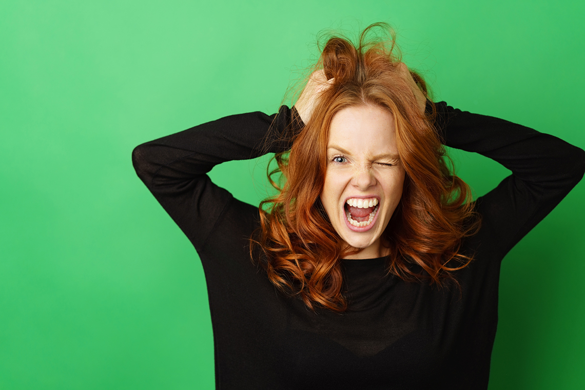 Frustrated redhead woman snarling at the camera as she tears at her hair with her hands over a green studio background with copy space
