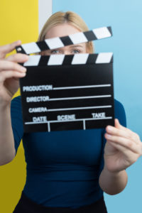 Young woman holding a clapperboard over colorful backgound